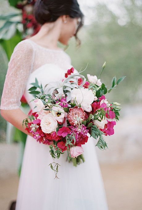 Bold Pink and White Bouquet of Roses, Protea, Ranunculus, and Greenery. A bold bouquet of garden roses, protea, ranunculus, stock, air plants, and greenery, created by Peony & Plum.