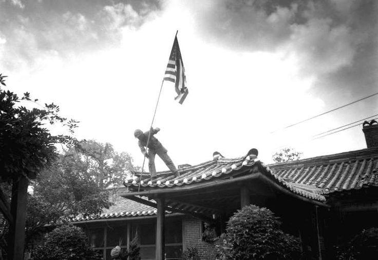 Amidst fighting in the compound, Marine Private First Class Luther Leguire, of the United States Marines, raises an American flag at the United States consulate in Seoul, Korea, September, 1950.