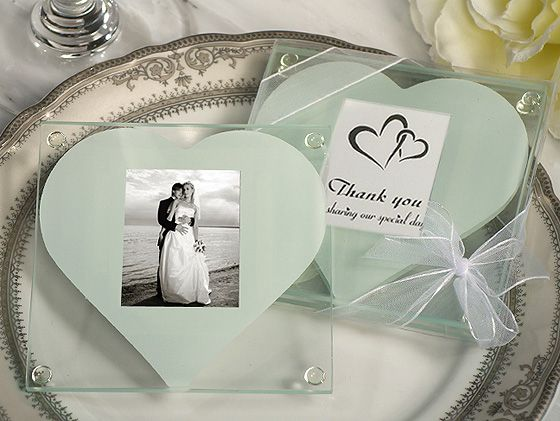 """Elegance and style! Every time your guests use these unique photo coasters they can be reminded of the fond memories from your special day. Our heart design photo coaster wedding favors will add a perfect finishing touch to your special event. Packaged in sets of 2 (each box has 2 coasters), these square glass photo coasters have a simply elegant white heart decal that holds a precious memory in the center. Each box contains a set of 2 coasters.Size: They measure 3.5"""" square and hold a 1.5"""" x..."""