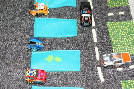 This is roll up playmat showing a road scene over a lake and fields, with pockets for cars. It has a polycotton cover and grey fleece lining. Hand embroidered and applique details are used to decorate.  Dimensions - Play mat - 35 x 42 cms Folded into roll - 35 x 15 cms Pockets - 12 cms deep Please note cars are not supplied. I do intend to adapt this design of a portable playmat into other play themes and art rolls. So watch this space for alternatives. Price - £15
