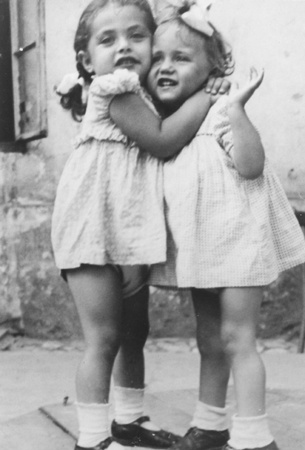 Close-up portrait of three-year-old Basia Israel hugging another young girl in the Krakow ghetto