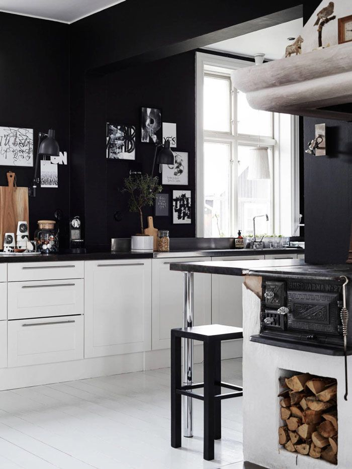 Modern black and white kitchen with an old wood stove.