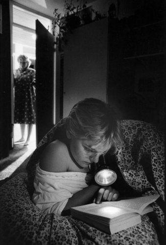 Jongeren. Een meisje ligt stiekem in bed met een zaklantaarn op haar boek gericht te lezen, haar moeder staat glurend in de deuropening. Plaats en datum onbekend.