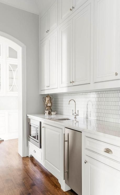White butler's pantry is fitted with white cabinets adorning polished hardware and finished with a stainless steel mini fridge and microwave fixed beneath a white marble countertop holding a small round sink and polished nickel gooseneck faucet in front of Ann Sacks Hive Tiles accenting stacked white upper cabinets.
