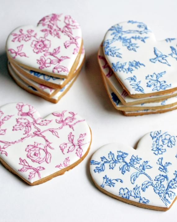 """Royal icing is a hard white icing made from egg whites, confectioners' sugar, and lime or lemon juice. It is used to prettify, pipe, and trim cookies and fruit cakes or to attach décor and candy (like the """"glue"""" used to embellish gingerbread houses). Patti Paige, owner of NYC's Baked Ideas, piped her heart-shaped cookies with botanical prints using blue and pink varieties."""