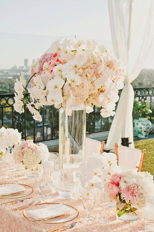 Pink and white is done right in this centerpiece of peonies, orchids, roses and hydrangeas.  I like this one note rose gold chair