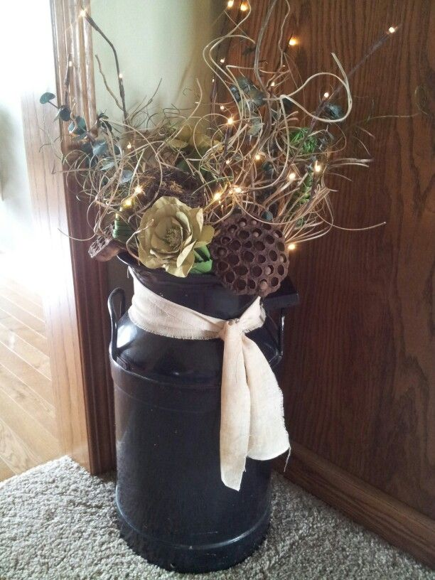 Old milk can filled w/ dried arrangement,lilly pods & lighted twig branch