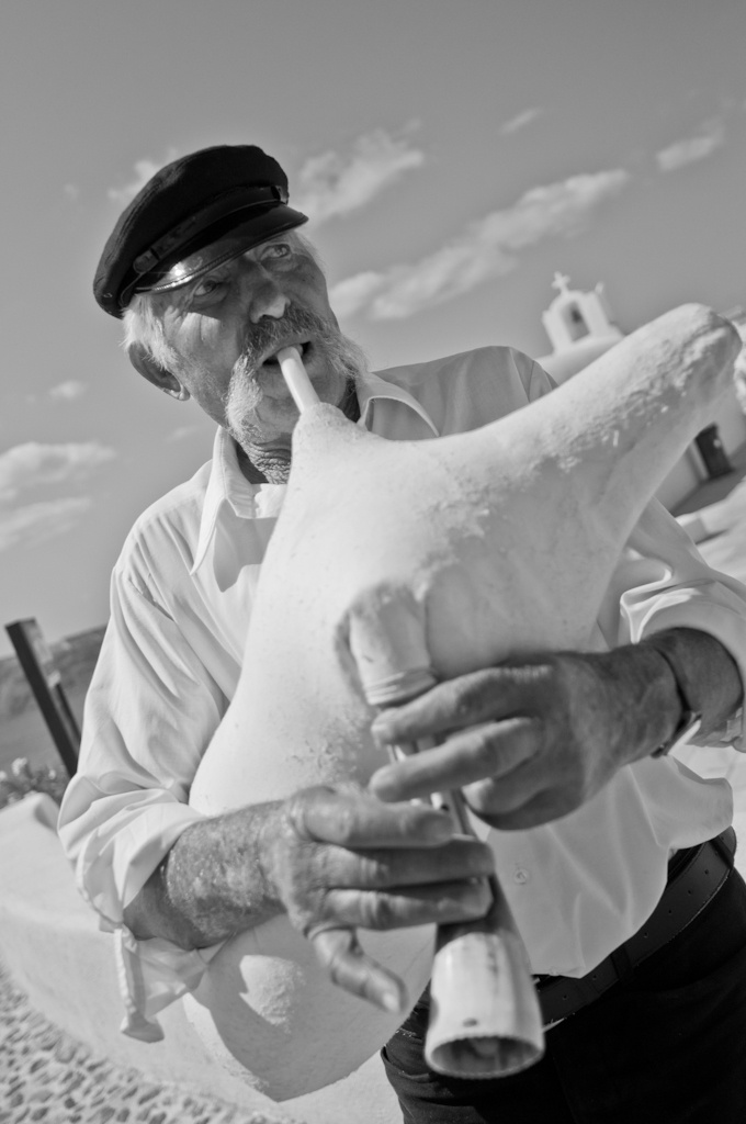 Greek man playing bagpipe from sheep in Santorini