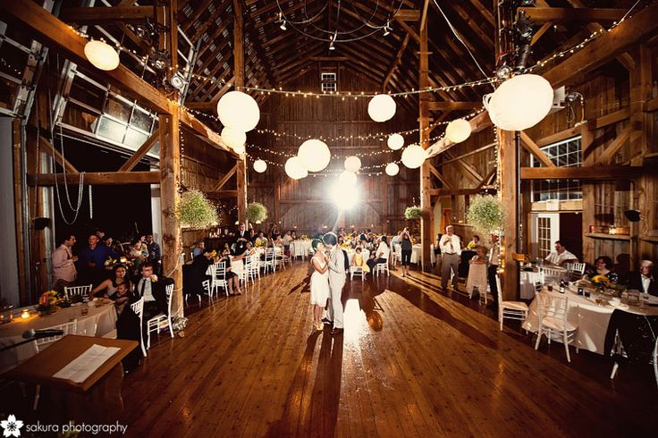 Barn interior wedding decor white chair wood floor globe lights
