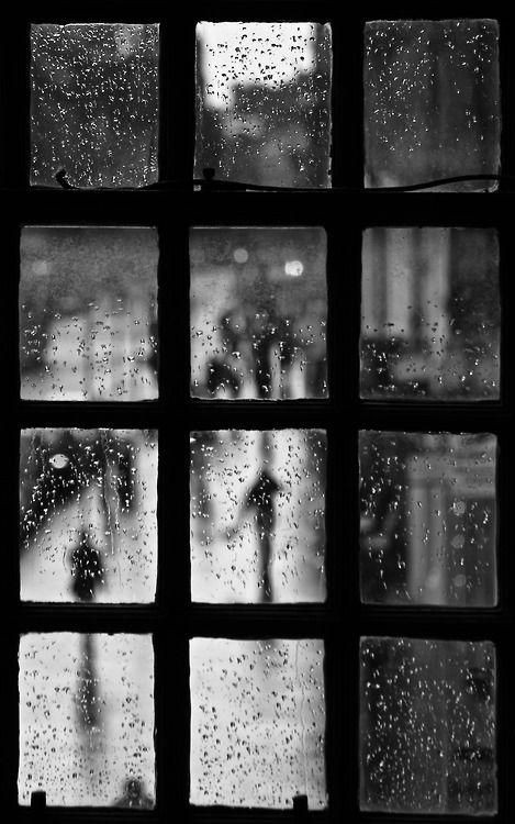 ...looking through a paned window to a street scene quiet and solemn with rain...