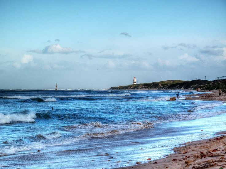 Shoreline on Cape Recife with a lighthouse in the background. Read about our drive on the southern coast of South Africa. -Travelationship