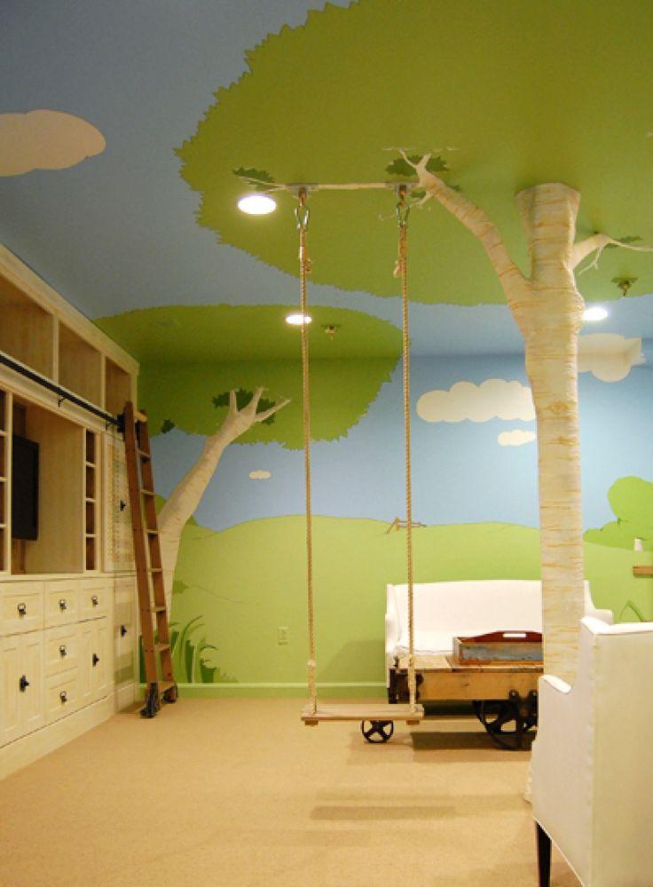 Originale e moderna cameretta per bambini, con altalena, dipinta con elementi naturali: prato, alberi e cielo. Un vero albero è stato posizionato nella stanza per dare un aspetto più veritiero al contesto