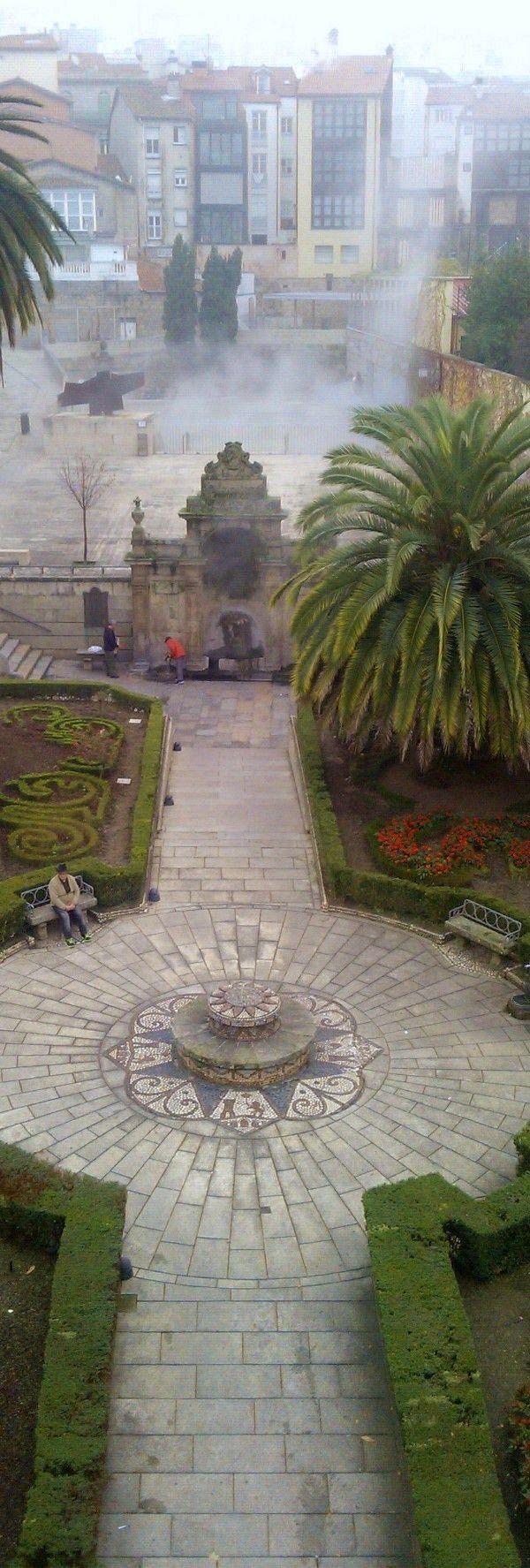 As Burgas de Ourense; manancial e, detrás, botando fume nun día frío, a piscina. Ourense. Galicia. Spain.