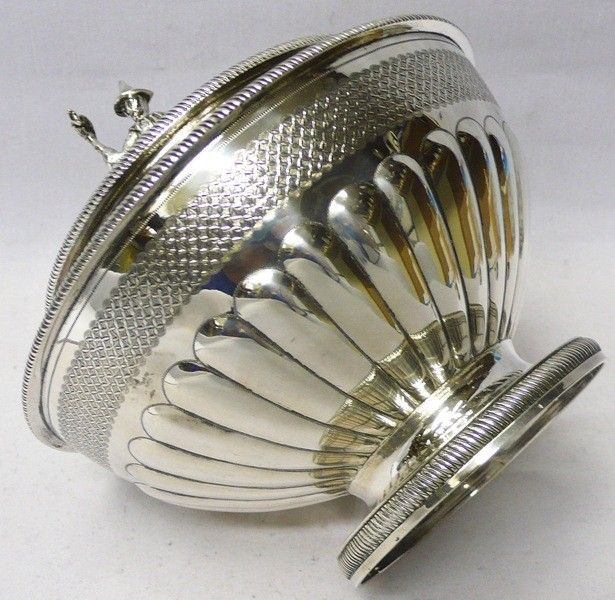A fine antique sterling silver tea caddy box of plain circular form having a central divider and lock (no key). An attractive feature is the decorative finial in the form of a Chinese gentleman holding a fish. The decoration is particularly fine, with gadroon edge borders and concentric bands of hand engraved leaf motifs, greek key design and basket weave. Weight 698 grams, 22.4 troy ounces. Height 16.5 cms. Diameter 16 cms. London 1807. Maker Peter & William Bateman.