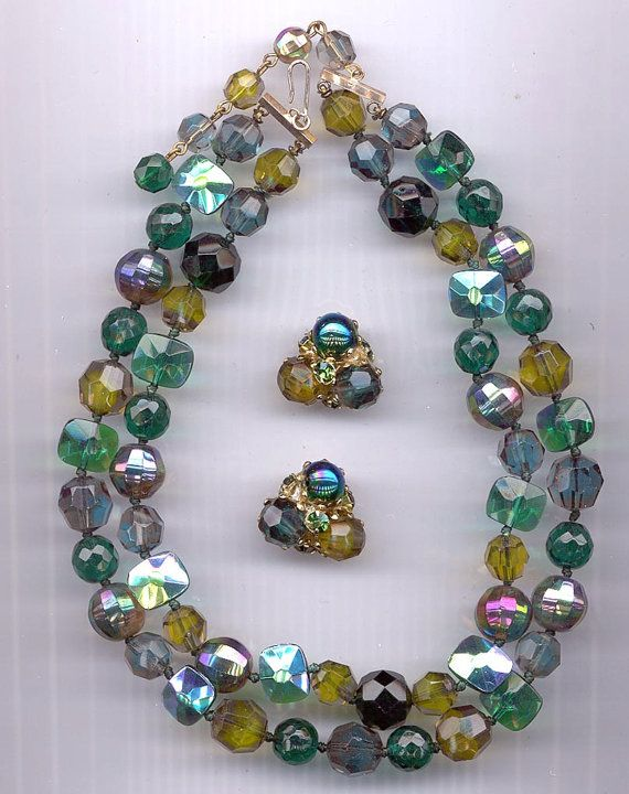This necklace and earring set is signed Vogue. Vogue was the trademark of the Park Importing Company of New York City on its beaded costume jewelry. The Vogue design house was founded in 1936 by Harold Shapiro, Jack Gilbert and George Grant, and ceased operations in 1973. Vogue costume jewelry is relatively scarce on the market.    This double-stranded necklace showcases a variety of vintage glass and crystal beads: emerald aurora borealis vintage West German faceted rectangles, vintage…