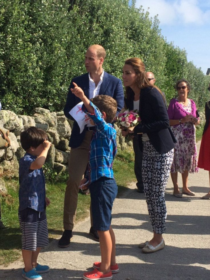 A young boy shows Kate the way as the royals arrive at St Martin's Community…