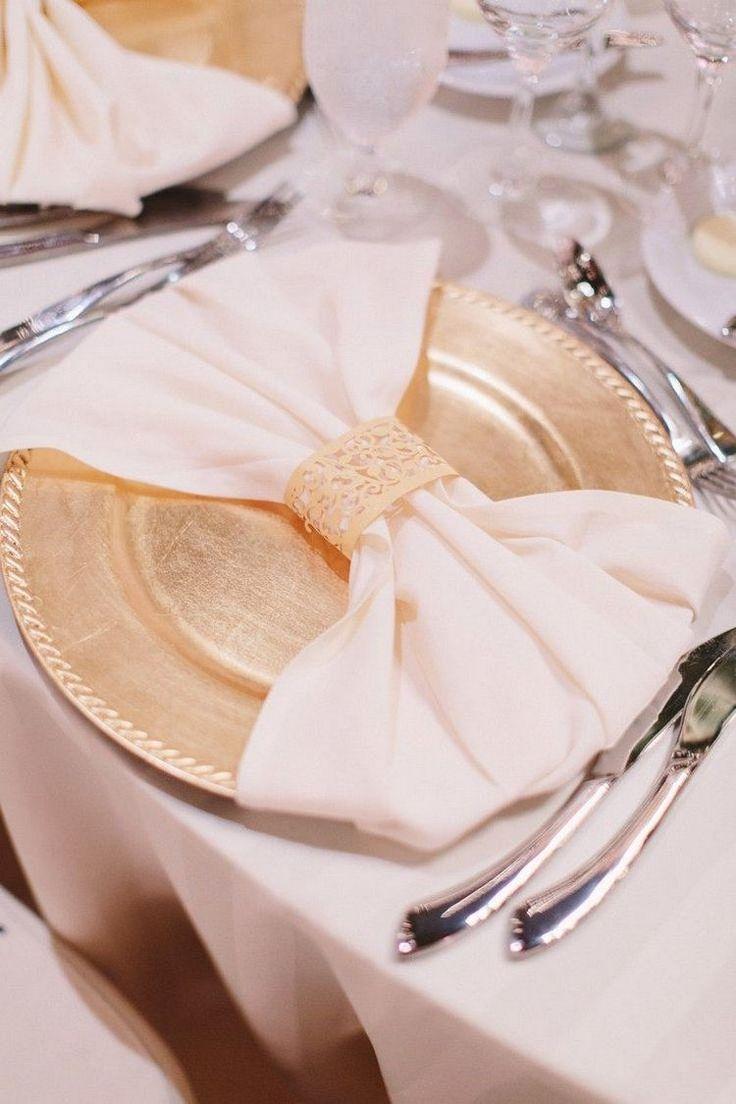 goldfarbener Teller und Serviette zu Schleife gefaltet