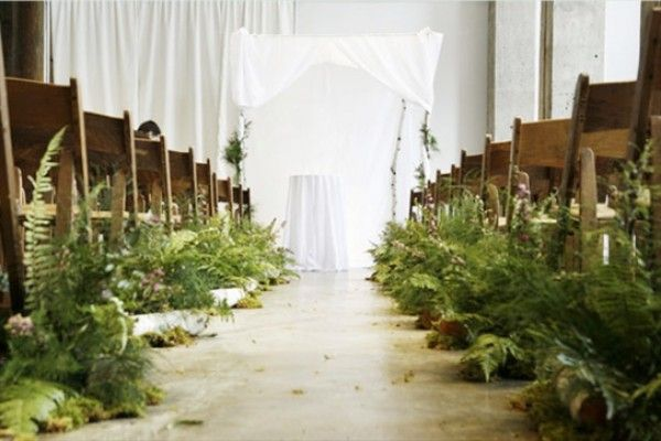 For a bohemian wedding, line the aisle with lush green plants like moss and ferns instead of flowers.