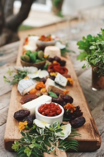 Wooden plank table runner displaying party food.