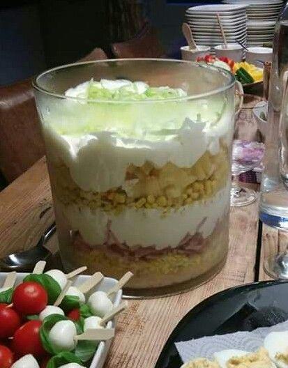 Laagjes salade Hier het recept voor de Laagjessalade: 1 pot selderij van Kuhne dan 4 hardgekookte eieren geprakt..bakje hamblokjes. .blikje maïs. .stukjes ananas. ..2 appels fijngesneden en een mengsel van geklopte slagroom en een halve pot yogonaise. .hiervan doe je de ene helft halverwege en de andere helft als laatste dan garneer je het nog met fijne preiringetjes.