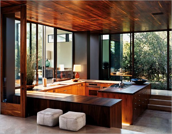 The two wings of the Radziner-Cottle House in California are joined by a spacious, sunken kitchen with a walnut ceiling and cabinets — and views to the pool and garden.