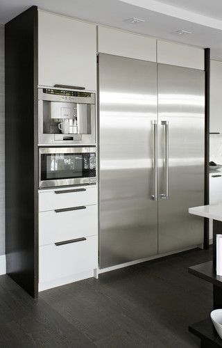 Stainless steel appliances contrast against white cabinetry.  Also integrated appliances (built into kitchen area).