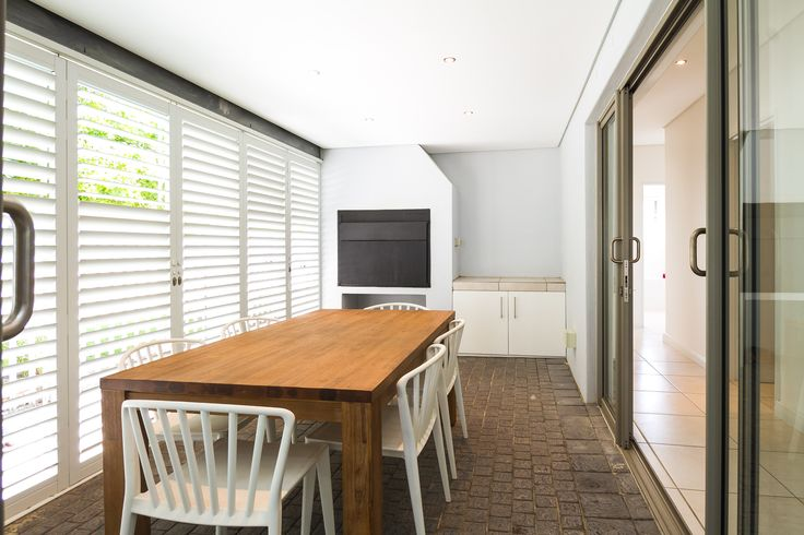 Across from the kitchen is an enclosed patio with built-in braai. This is perfect for entertaining guests in both the warm months (the shutters can open) and the cooler months.