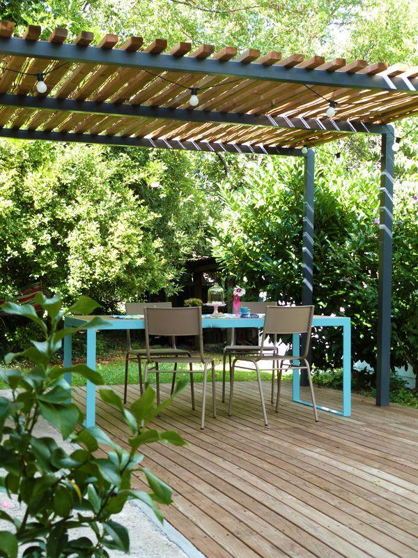 Pergola métal, terrasse bois et table de jardin design.