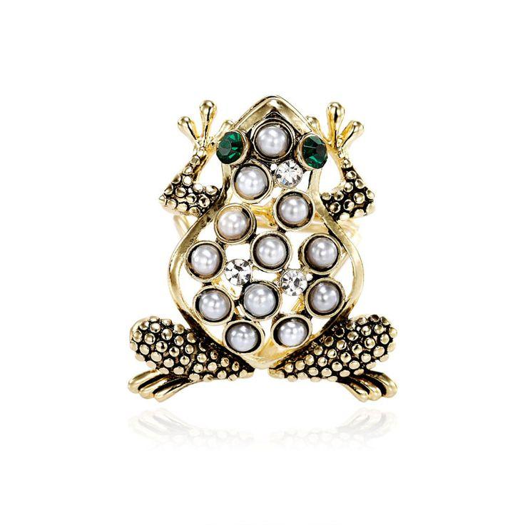 Módny prsteň na hodvábnu šatku alebo šál s motívom zvieraťa. Ozdoba nesie dekoráciu roztomilej žaby, ktorej telo je posiate perlami a oči sú vyrobené zo zeleného brúseného skla. Celá ozdoba obsahuje trio krúžkov, slúžiace na prevlečenie hodvábnej šatky alebo šálu. Prstenec je druh spony na šatky, ktorý obsahuje trojitý krúžok na prevliakanie šatiek a šálov. Skúste byť originálna a ozdobne si svoju hodvábnu šatku alebo hodvábny šál.