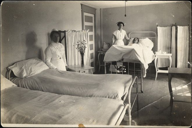 A photograph of Nurse Annie Saunders and another nurse sanding in a small ward in the Cobalt Hospital