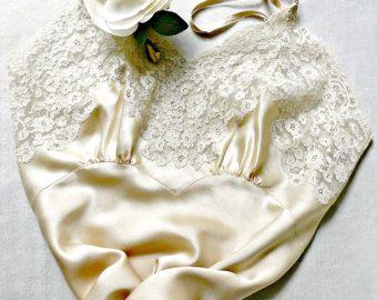 Cette beauté circa 1940 est en biais coupé dans une teinte magnifique, riche de pêche charmeuse satin de soie avec des nuances de roses. V inversé sous buste couture et pinces poitrine verticale fournir un soutien. Non réglable 1/8 de large sangles en soi. Le décolleté en V-cut et coupe droite arrière sont appliqued avec une frontière extravagante de dentelle florale de coton écru. Le motif de dentelle est repris dans le swag appliqued bel bordure droite hanche et vallonné 5» profond fl...
