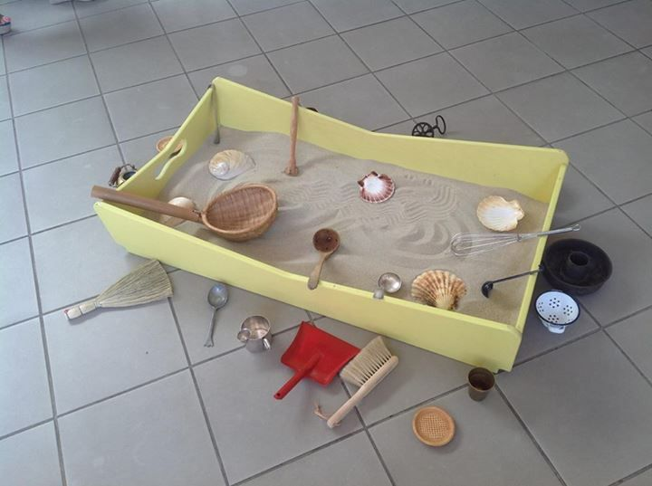 Sand tray on the floor, with tools for exploring (Asilo Nido Bianconiglio, Infernetto)