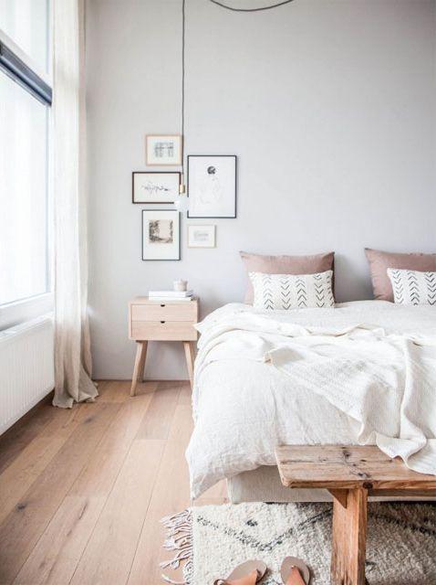 Dormitorio nórdico en tonos blanco, gris, rosa y madera clara. Pequeña alfombra tejida en telar y pie de cama rústico. Foto: Avenuelifestyle