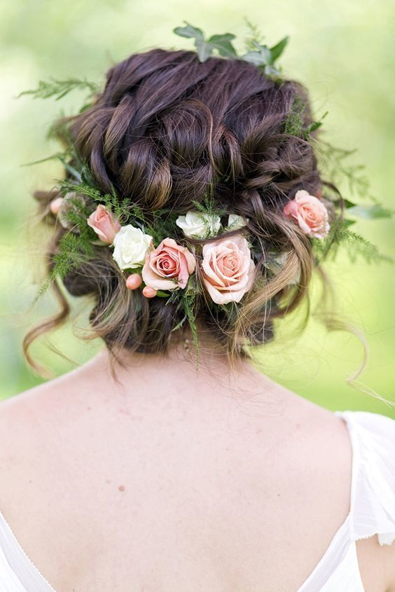 This low updo gives off the appearance that the flowers are beautifully woven into the hairstyle. This is perfect for any outdoor or even an indoor wedding.
