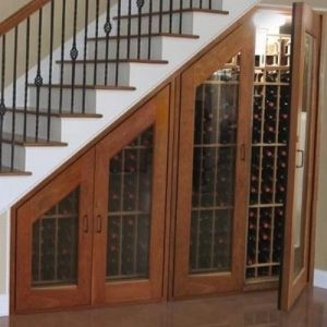 Custom wine racks under stairs with glass doors, clever uses of empty space