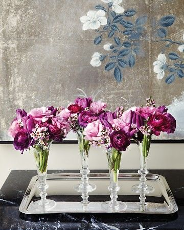 Tulips, lisianthus, waxflowers, and ranunculus nestled in Champagne flutes -- totally wedding-worthy don't you think?