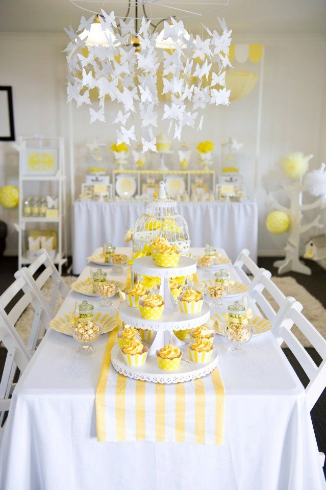 Yellow & White High Tea Party- The main seating table is beautifully decorated with a yellow and white striped table runner, a white antique bird cage as the centerpiece and lovely yellow flowers arranged in white containers. Cupcakes with matching wrappers and flags were displayed on simple white cake stands and the white paper butterfly chandelier is the perfect accent...wow!