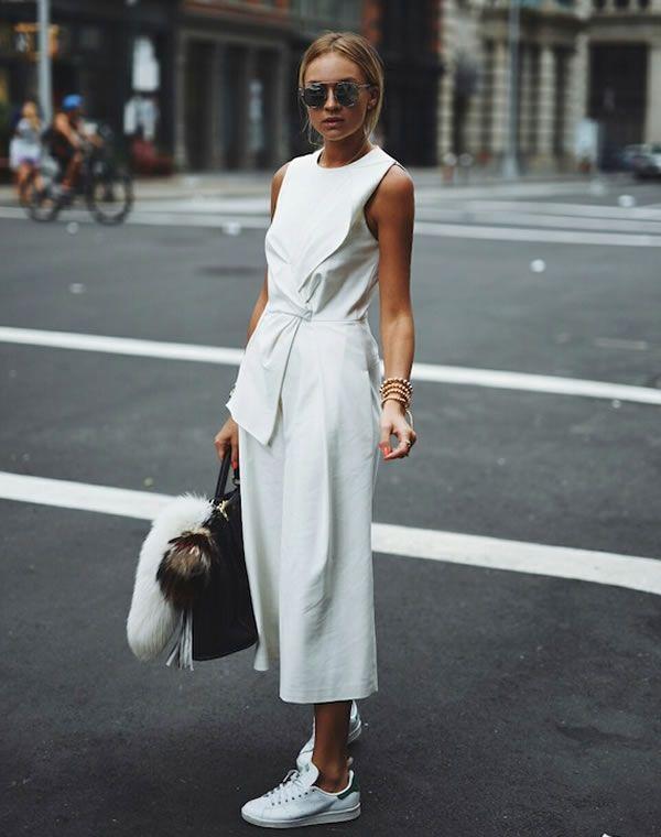As duas maiores tendências dos últimos tempos, o macacão e a calça culotte se uniram para formar o macacão culotte. O resultado foi uma peça sexy e descolada ao mesmo tempo, como nesse look de street style com macacão culotte branco e tênis.