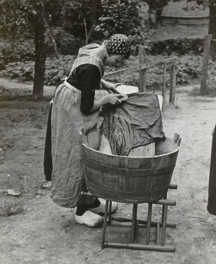 Vrouw in Staphorster streekdracht bij wastobbe. Ze is gekleed in werkdracht. De vrouw draagt een schort die gemaakt is van een afgedankte meelzak. 1950 #Overijssel #Staphorst