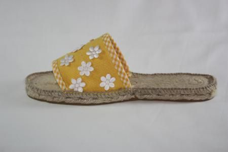 Chancla de esparto color amarillo con flores blancas.