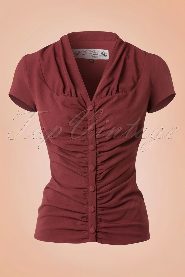 The40s Rosina Blouse in Burgundy Crêpeby Bunny is a classic blouse with endless combination possibilities!This beauty will turn any outfit into a splendor one! Beautifully fitted pleated blouse featuring a V-neckline, short sleeves and a row of burgundy fabric buttons.Made from a light stretchy, supple burgundy crêpe fabricfor a typical 40s look and feel ;-)Long enough to pair with regular trousers but super fabulous when matched with a high waist sk...
