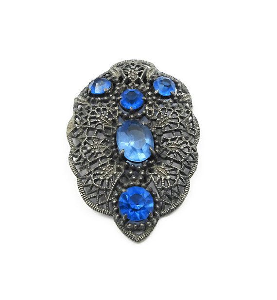 Art Deco silver tone filigree metal blue rhinestone dress or scarf clip. Age: estimated circa 1930s - 40s, late art deco era. Hallmarks: there are no hallmarks. Measurements: it is approximately 2-1/4 tall x 1-1/2 wide. Condition: it is in overall good condition consistent with age. There is no damage, only light surface wear. The clip mechanism functions properly.  We offer free shipping within the United States. International shipping rates are as listed.  To see more vintage and ...