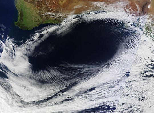 "An anticyclone is a weather phenomenon defined as ""a large-scale circulation of winds around a central region of high atmospheric pressure, clockwise in the Northern Hemisphere, anti-clockwise in the Southern Hemisphere"". Effects of surface-based anticyclones include clearing skies as well as cooler, drier air. Fog can also form overnight within a region of higher pressure."