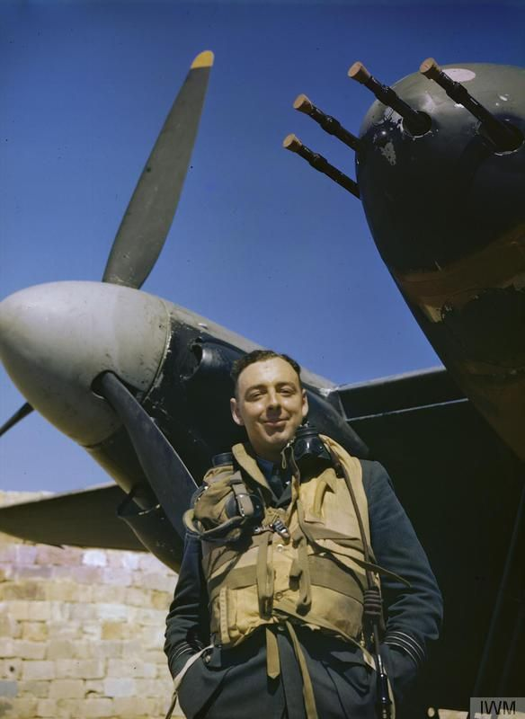 The CO of No 23 Squadron, Royal Air Force, Wing Commander John B Selby, DSO, DFC, framed against the nose and engine of his De Havilland Mosquito II aircraft `P-Peter', Malta, 27 June 1943. The four .303in machine guns are corked to prevent dirt damaging them.