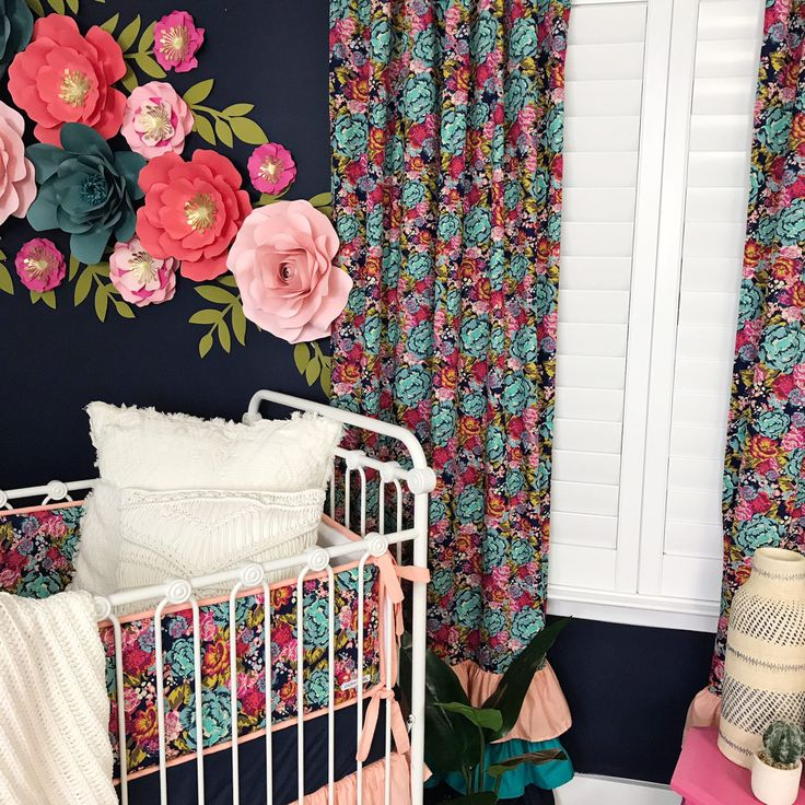 This dark floral navy nursery is the perfect combination of navy, coral, and pink that will grow with her room design for years to come.