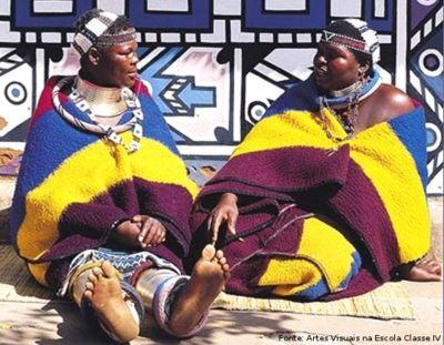 As mulheres da tribo Nbedele, localizada na África do Sul, andam com mantos coloridos amarrados nas costas, como vestimenta. <br/> Palavras-chave: mulheres, tribo Ndebele, vestimenta, cobertores, Africa do Sul