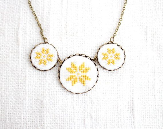 Cross stitch necklace with three yellow ethnic ornament in bronze