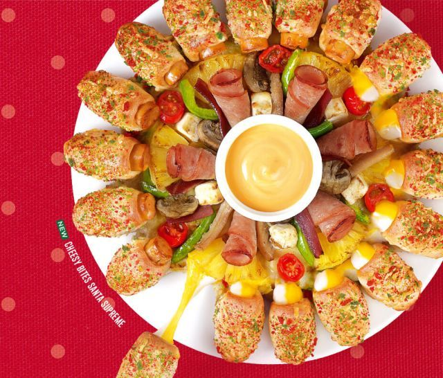 Pizza Hut Singapore's Cheesy Bites Santa Supreme features Cheesy Bites sprinkled with red and green parmesan-flavored breadcrumbs. topped with an arrangement of honey-baked turkey ham, turkey bacon, bell peppers, cherry tomatoes, pineapples, and a medley of mushrooms. Serving as the centerpiece is a cup of jalapeno cheese sauce.
