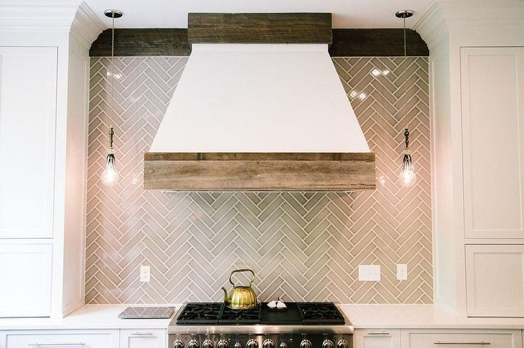 A white French kitchen island accented with wood trim lines a gray herringbone tile backsplash illuminated by filament light pendants placed over a stainless steel stove.