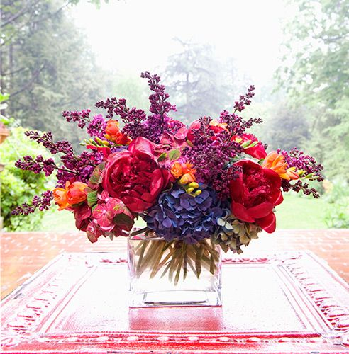 Vibrant wedding or party fresh flower centerpiece in fuschia, purple, lavender and orange